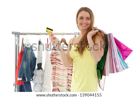Beautiful female shopper with shopping bags, credit card and clothes on hangers on a white background.