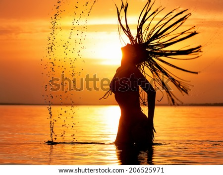 Beautiful female silhouette with splash of sea water against  sunset background - stock photo