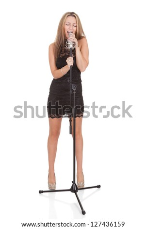 Beautiful female singer with a microphone isolated on white - stock photo