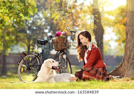 Beautiful female sitting down on a green grass with her dog in a park - stock photo