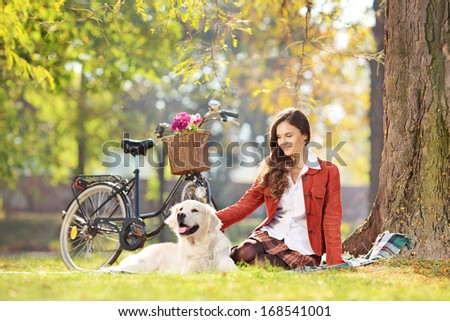 Beautiful female sitting on a green grass with her dog in a park - stock photo
