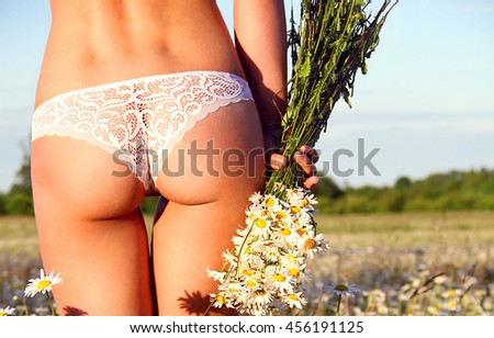 Beautiful female slim body. Beauty part of female body. Woman's shape with clean skin. Healthy lifestyle. Ideal waist, perfect buttocks and legs, sexy back. The sexy girl with a bouquet of camomiles. - stock photo