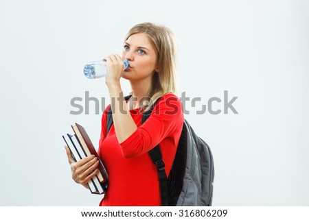 Beautiful female student is drinking water.Healthy refreshment for student - stock photo
