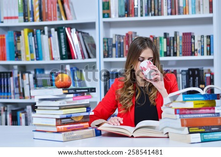 beautiful female student learning in the library and drinking coffee