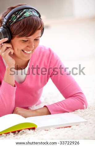 Beautiful female student listening to music and reading