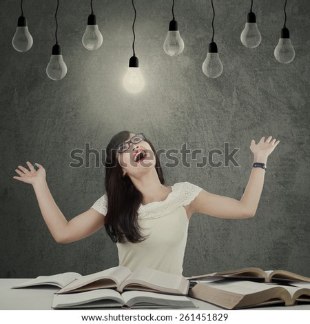Beautiful female student looks happy while looking at the bright lightbulb, symbolizing she get a solution - stock photo