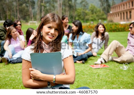 Beautiful female student outdoors with a group behind - stock photo