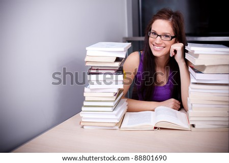 Beautiful female student studying hard in the library - stock photo