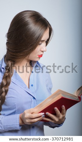 Beautiful female student studying with red book, isolated on background
