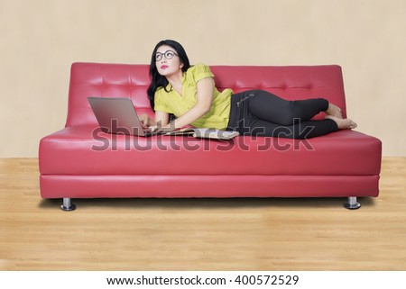 Beautiful female student typing on the laptop with a book on the sofa and imagine something