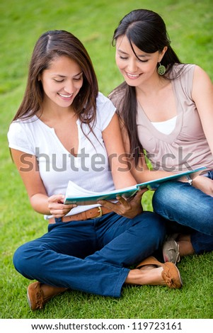 Beautiful female students studying outdoors looking happy