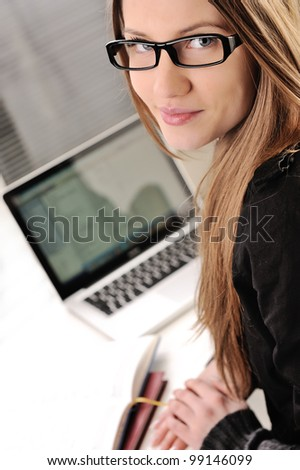 Beautiful female teenager with laptop and books - stock photo
