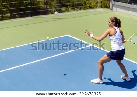 Beautiful female tennis player in action, hitting a forehand