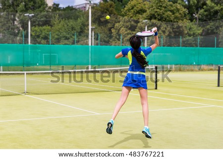 Beautiful female tennis player in action wearing a sportswear during a match on a court outdoor in summer or spring