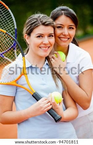 Beautiful female tennis players at the court smiling - stock photo