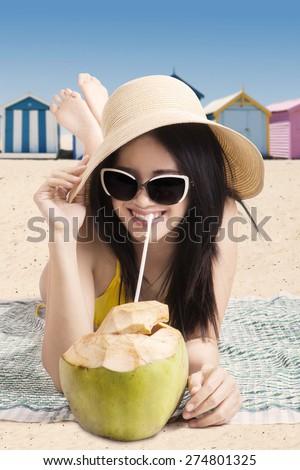 Beautiful female tourist lying on the coast while enjoying coconut water and wearing bikini - stock photo