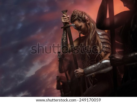 Beautiful female warrior elf with sword over cloudy sky - stock photo