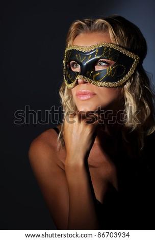 Beautiful female wearing mask, mysterious girl at masquerade, stylish woman portrait studio shot, glamor and fashion lifestyle - stock photo