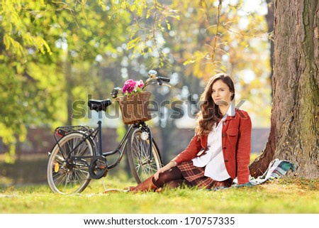 Beautiful female with bicycle sitting in a park and looking at camera - stock photo