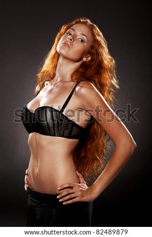 Beautiful female with long red hairs, on black background - stock photo