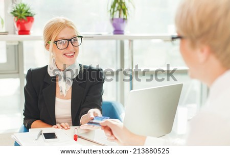 Beautiful female worker issuing credit card to a customer - stock photo