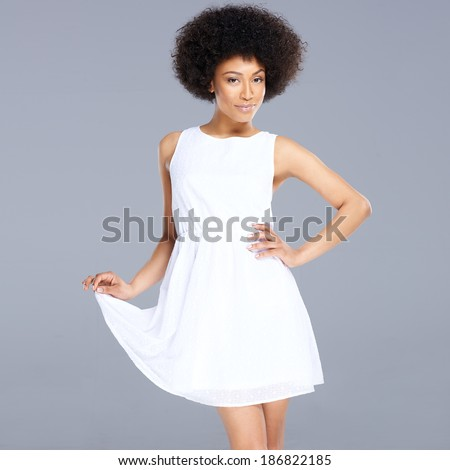 Beautiful feminine African American woman in a fresh white short summer dress posing holding up one edge of the flared skirt with a smiling provocative expression, on grey - stock photo