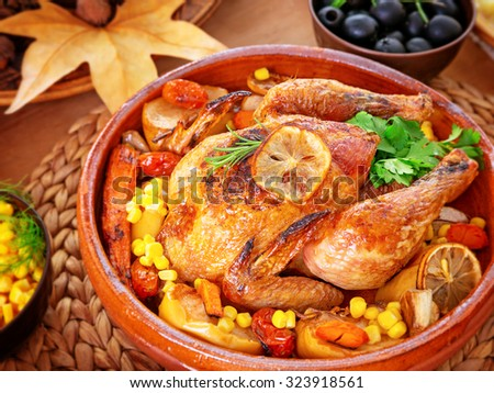 Beautiful festive food still life, tasty crispy chicken with baked vegetables on the centerpiece of table, traditional family dinner in Thanksgiving day  - stock photo