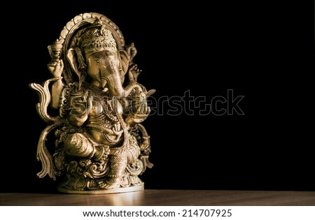 Beautiful figurine of Hindu god of wisdom, knowledge and new beginnings Ganesha against dark background. - stock photo