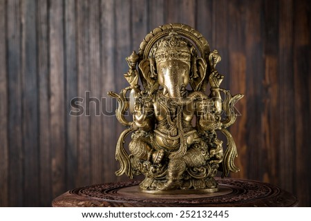 Beautiful figurine of Hindu god of wisdom, knowledge and new beginnings Ganesha against wooden background. - stock photo