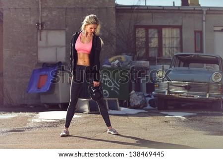 Beautiful fiitness woman lifting kettlebell outdoor - stock photo