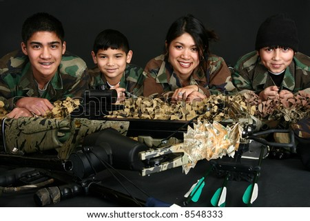 Beautiful Filipino woman and her three sons in camo and hunting gear. - stock photo