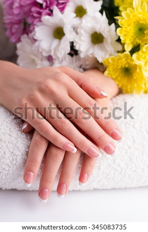 Beautiful fingers with French manicure on a towel on the background of flowers. Manicure in a beauty salon.