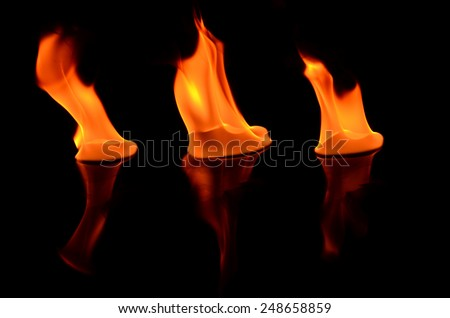 Beautiful fire flames reflected in black table - stock photo