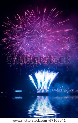 Beautiful fireworks in the night sky with reflection on water - stock photo