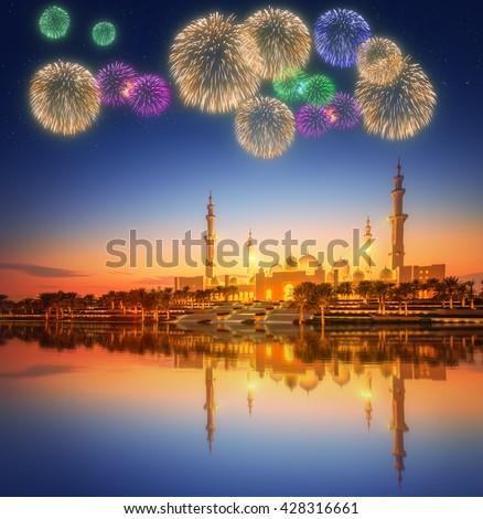 Beautiful fireworks under Sheikh Zayed Grand Mosque at dusk, Abu-Dhabi, UAE - stock photo