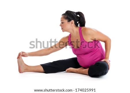 Beautiful fit pregnant woman doing a leg stretch on the floor isolated on white background - stock photo