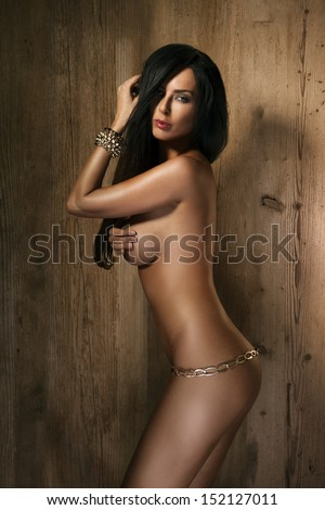 Beautiful fit sexy topless woman wearing gold chain  - stock photo