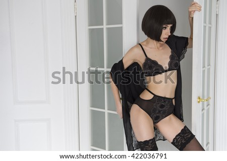 Beautiful fit slim brunette woman with black bob haircut and seductive make up in black sexy lingerie in loft home rich interior. Copy space - stock photo
