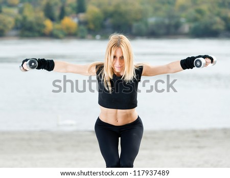 Beautiful fit woman exercising  outdoors - stock photo