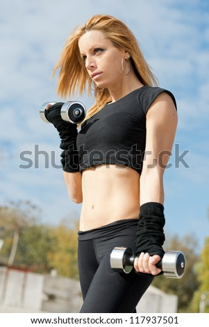 Beautiful fit woman exercising  outdoors over a sky background - stock photo