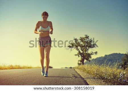 Beautiful fit woman in sport shorts running on a road at sunrise or sunset. Healthy lifestyle concept. Toned with warm instagram like filter. - stock photo