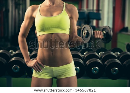 Beautiful fit woman working out in gym - girl in fitness - stock photo