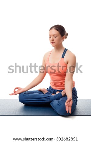 Beautiful fit yogini woman meditating  in yoga asana Padmasana (Lotus pose) cross legged position for meditation with Chin Mudra - psychic gesture of consciousness isolated on white background - stock photo