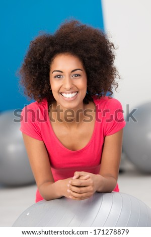Beautiful fit young African American woman in a gym leaning on a silver Pilates ball smiling at the camera as she relaxes between exercises - stock photo