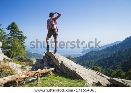 Beautiful fit young woman hiking up a mountain and enjoying the panoramic view on the island of Thassos, Greece. - stock photo