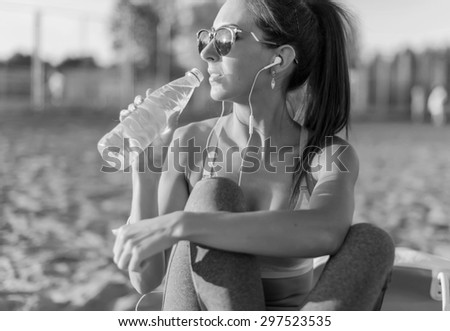 Beautiful fitness athlete woman drinking water after work out exercising on summer in beach outdoor portrait - stock photo