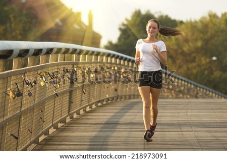 Beautiful fitness girl runner working out jogging. Running in the City.