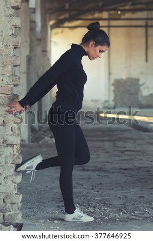 Beautiful fitness girl stretching and exercising in abandoned building. - stock photo