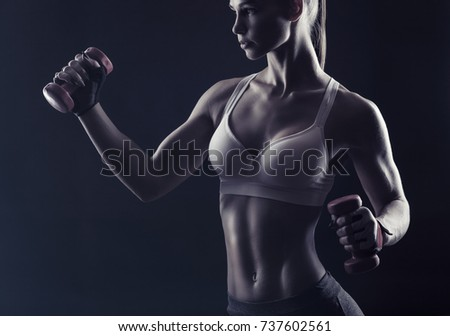 Beautiful fitness girl with dumbbells against a dark background