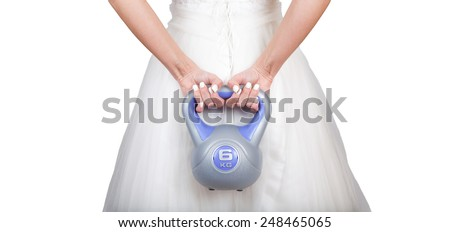 Beautiful fitness model bride wearing wedding dress (grown) and training with dumbbell (weight) - Weight loss workout before the day - isolated on white background - stock photo